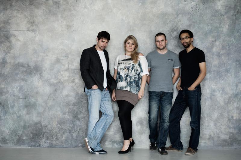 """Vier Musiker der Band """"Popzone"""" vor Betonwand"""