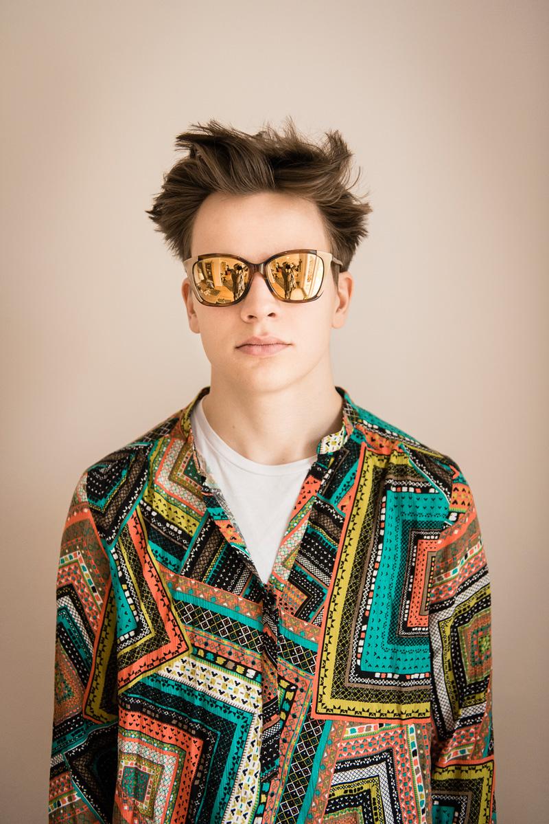 Junger Mannes in gemustertem Hemd und mit verspiegelter Sonnenbrille