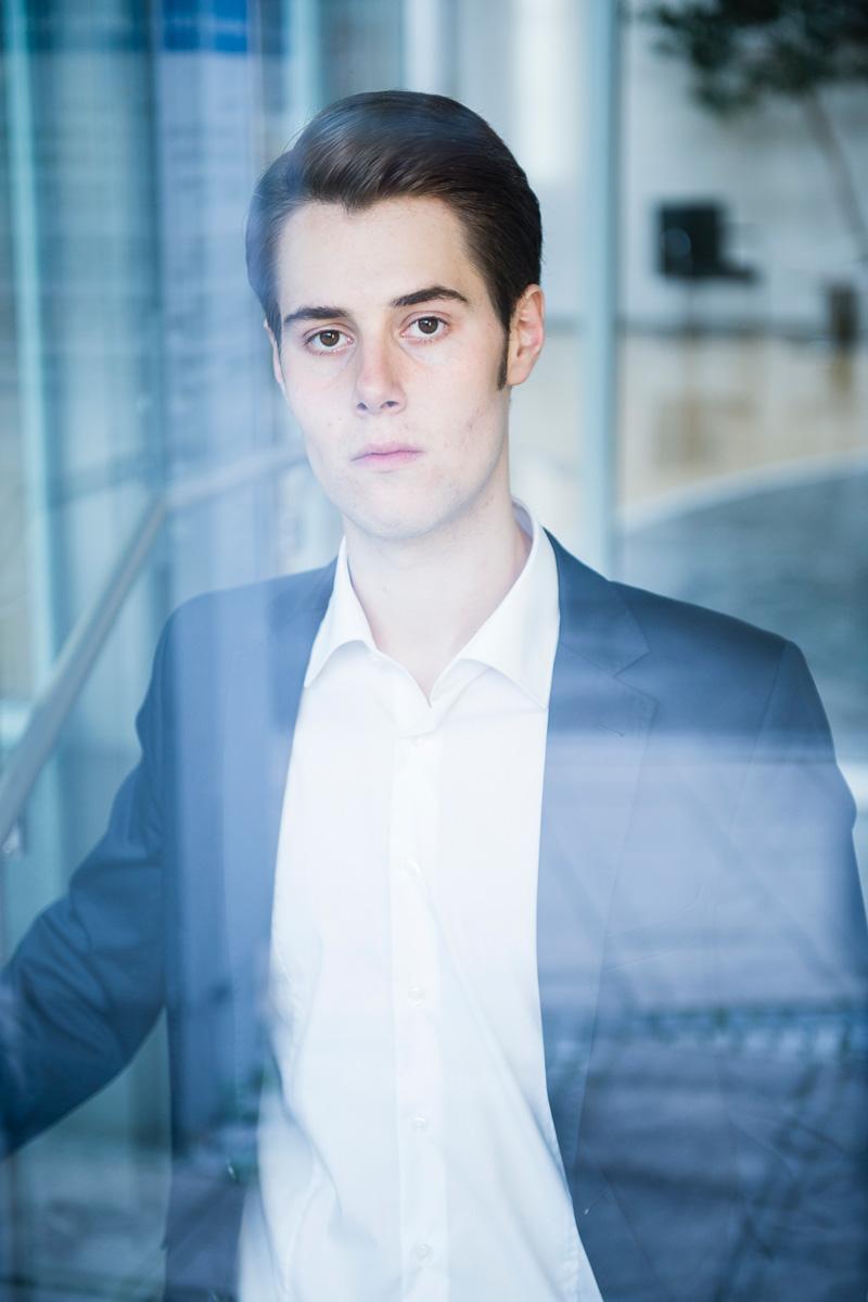 Junger Mann im Anzug hinter Glasfenster