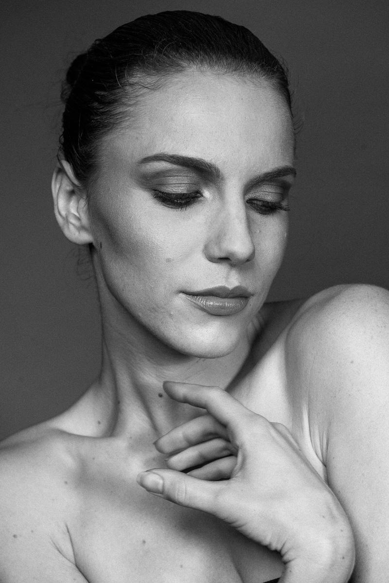 Junge Frau mit intensivem Augen-Make-up blickt zu Boden